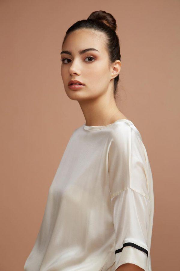 maglia dalla forma classica, con un tocco di femminilità. Questo capo è realizzato in raso di seta leggero e profilato con dei piccoli bordi neri che aggiungono eleganza